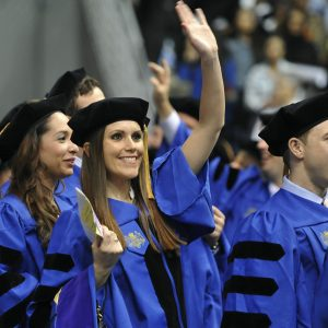 A 2013 graduate waves to the crowd.