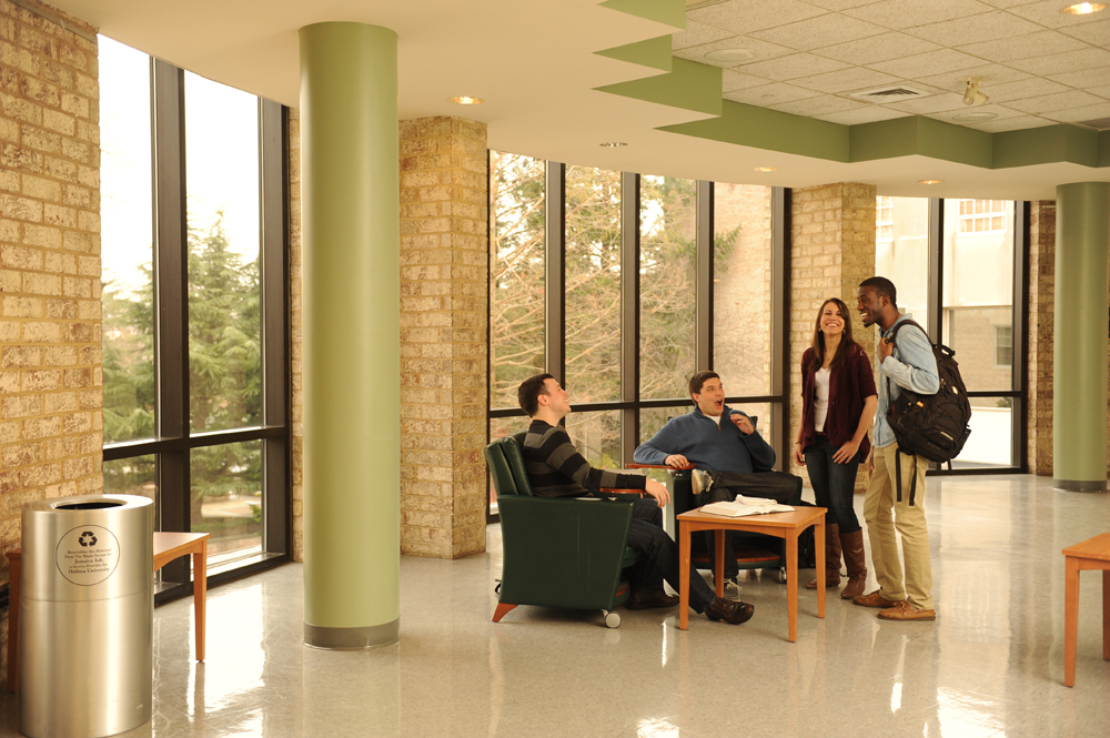 A group of students talking in the atrium between classes.