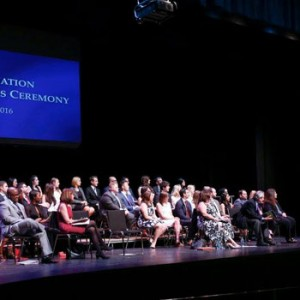 Photo of student award winners, Teacher of the Year Miriam R. Albert and Dean Eric Lane seated onstage at the 2016 Graduates Celebration and Awards Ceremony as Student Bar Association President Justin Worth delivers remarks