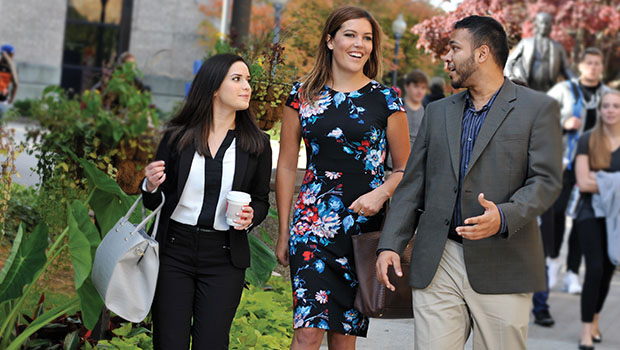3 Hofstra Law students in professional attire engaged in conversation while walking on campus
