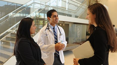 Photo of two Hofstra Law students talking with a medical student in the Donald and Barbara Zucker School of Medicine at Hofstra/Northwell