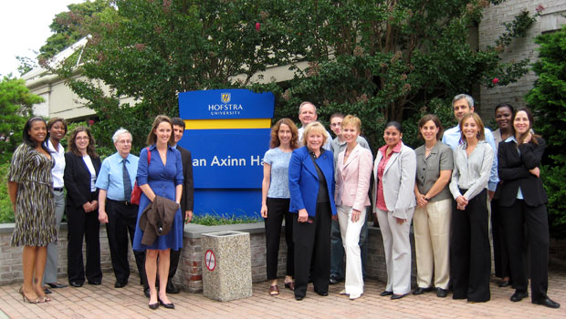 Photo of Hofstra Law alumna Joan Axinn '76 (second to the right of the sign) outside Joan Axinn Hall, the home of Hofstra Law's Clinical Programs, with Dean Nora Demleitner (third to the right of the sign) and Clinical Programs faculty, staff and students