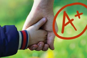 Image of an adult holding a child's hand, with a circled A+