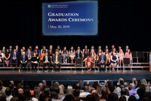 Photo of student award recipients and speakers on the stage at the John Cranford Adams Playhouse for the Hofstra Law Class of 2019 Graduates Awards Celebration on May 20, 2019